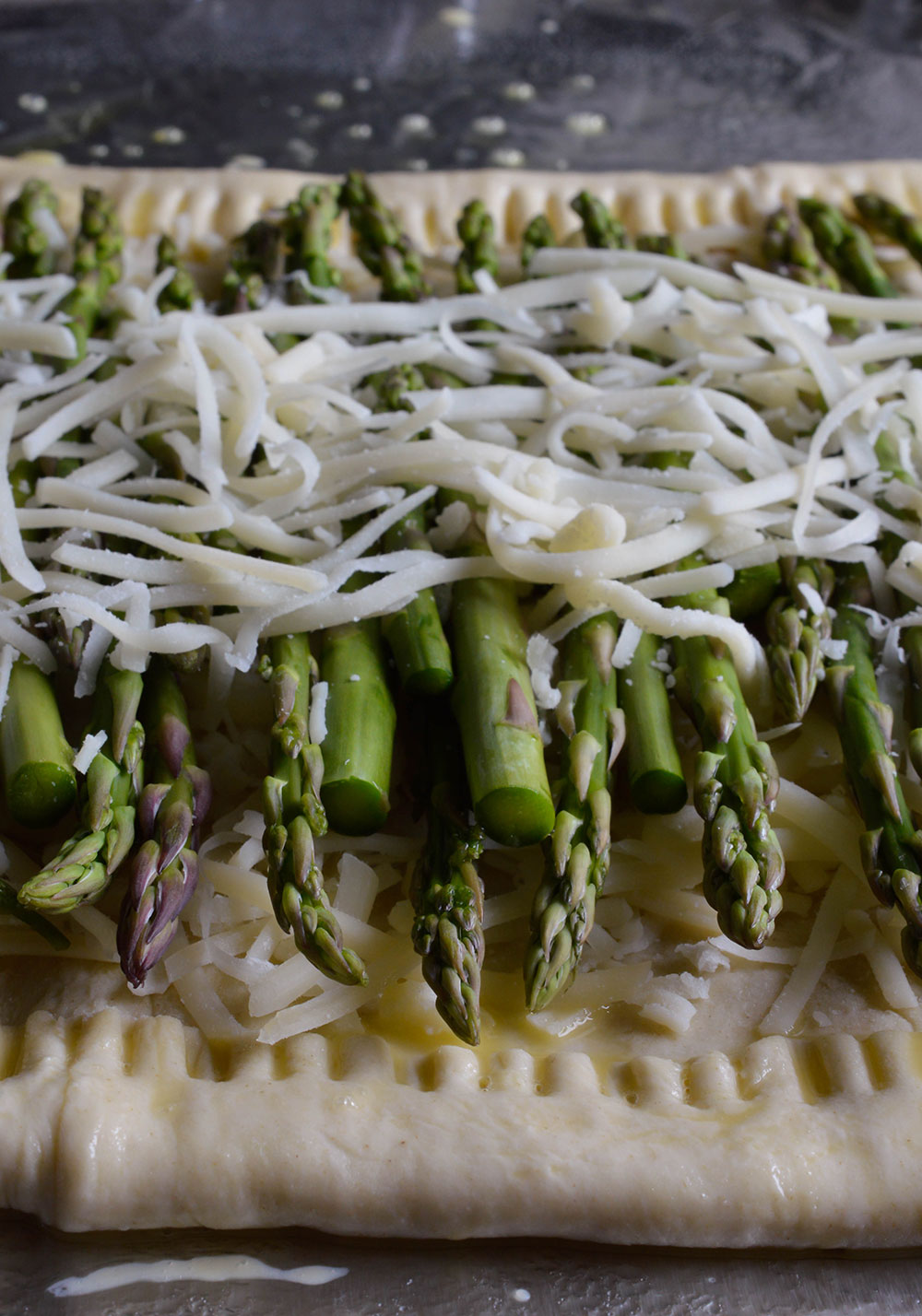 This Asparagus and Prosciutto Puff Pastry is perfect as an appetizer or meal! A simple recipe with flavorful ingredients. Golden puff pastry topped with fresh asparagus, cheese, prosciutto and drizzled with a honey mustard sauce!