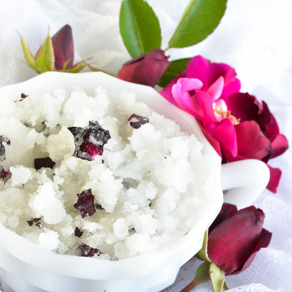 Rose Scented DIY Body Scrub Recipe - This homemade sugar scrub has a delicate rose smell and real rose petals. The perfect gift for Mom. Or give the wife a luxurious spa day at home!