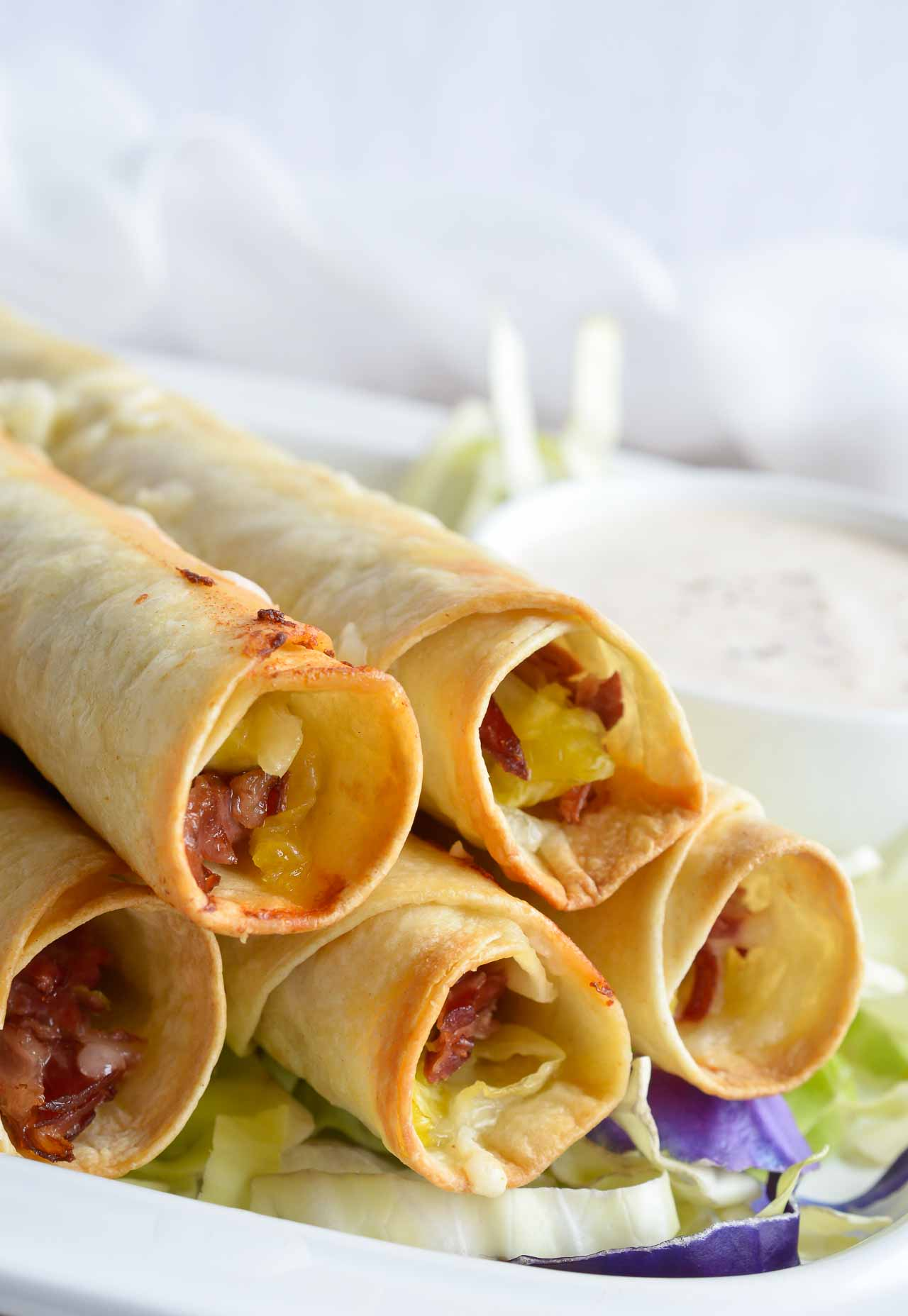 If you have leftover corned beef after Saint Patrick's Day, make this Reuben Stuffed Baked Taquitos Recipe! These homemade taquitos are filled with corned beef, sauerkraut and swiss cheese. Dip them in thousand island dressing for the ultimate meal or snack!