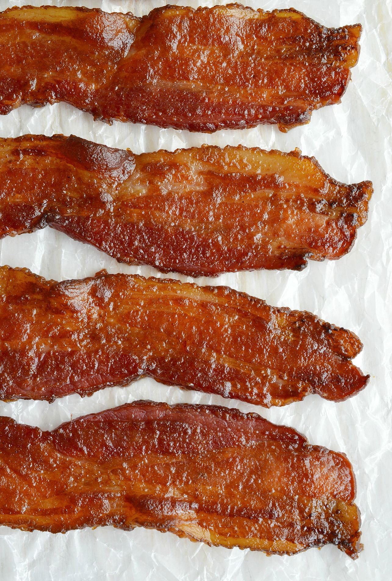 This Candied Bacon Recipe should be illegal. It IS that good! Just 3 ingredients make a glazed bacon that is sweet, salty, crispy and super addictive. This apple butter glazed bacon is perfect for any meal or occasion!
