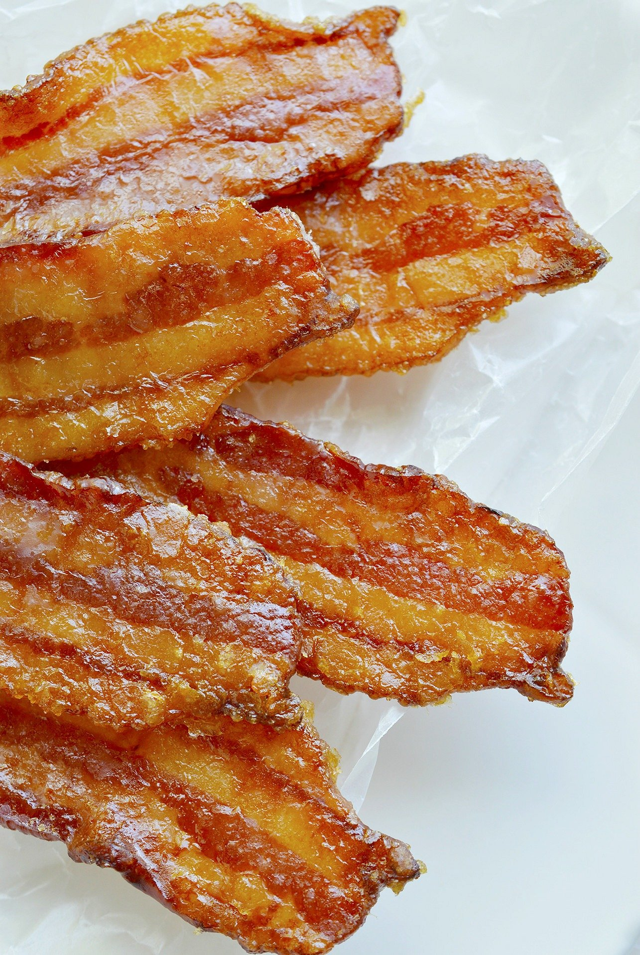 Sugary sweet bacon is the ultimate indulgent treat! This Brown Sugar Maple Bacon Recipe has the best of sweet and salty. Candied bacon will change your life! It is that good.