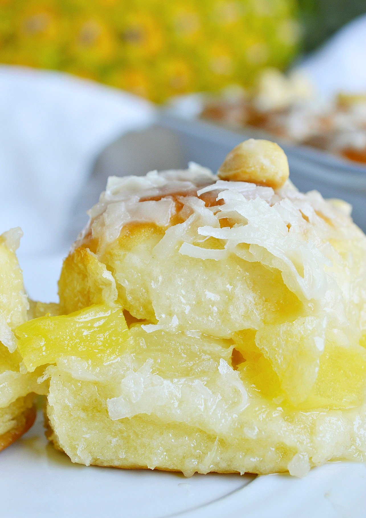 Pineapple Coconut Hawaiian Sweet Rolls in 20 minutes! Yes, it is possible. Sweet Hawaiian rolls stuffed with pineapple and coconut then drizzled with a pineapple glaze. Top with macadamia nuts for the ultimate tropical inspired dessert recipe.