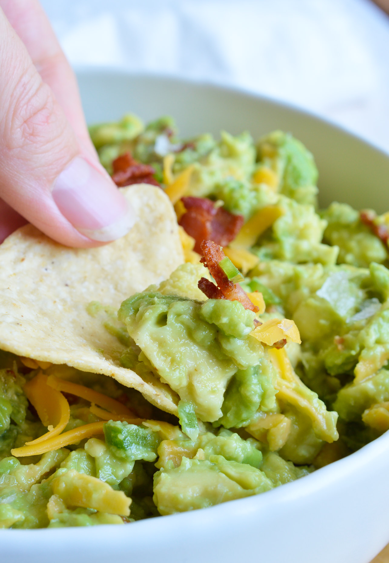 Guacamole just got even better with bacon, cheddar cheese and jalapeños. This Jalapeño Popper Guacamole Recipe is the perfect appetizer for barbecues, parties, game day or just to cure your guac craving! And what doesn't taste better with a little cheese and bacon!?!?
