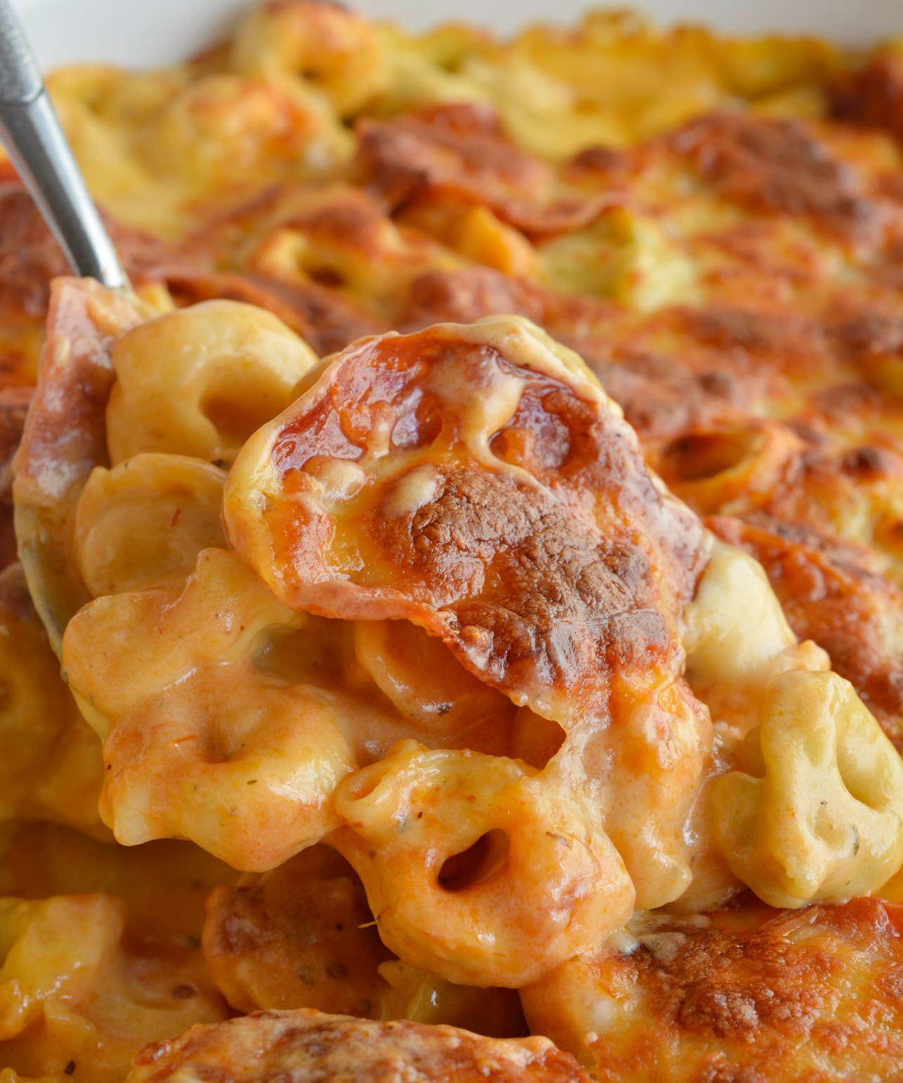 If you love macaroni & cheese and pepperoni pizza you will flip for this Cheese Tortellini Pepperoni Pizza Casserole Recipe! This tortellini mac & cheese is combined with the flavors of pepperoni pizza then baked to bubbly, cheesy perfection. This dinner is sure to become your family's new favorite comfort food!