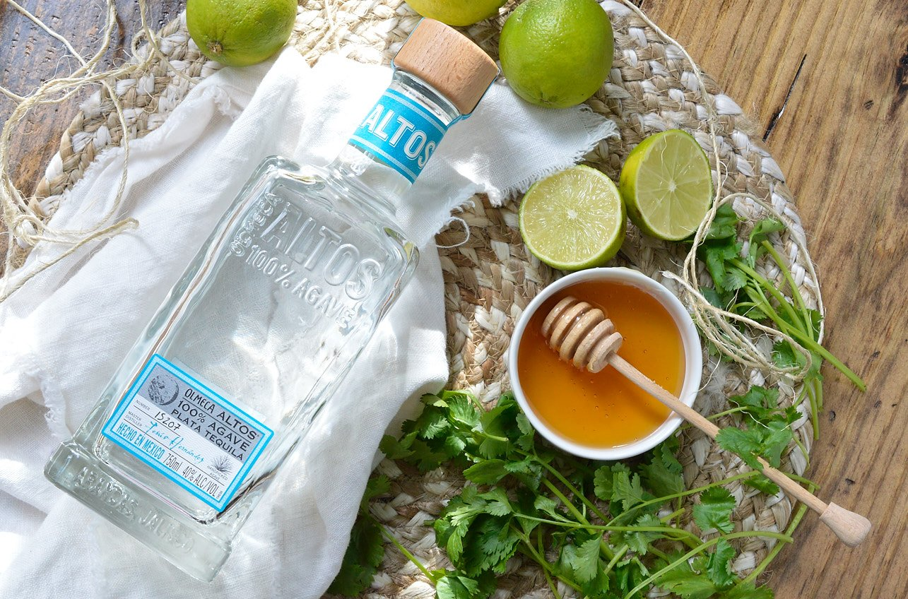 ingredient photo with tequila bottle, honey, limes and cilantro