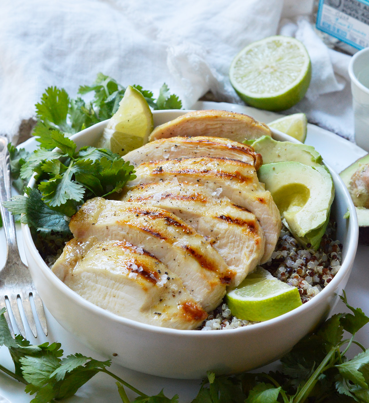 sliced tequila lime chicken breast over quinoa with limes, cilantro and avocado on the side