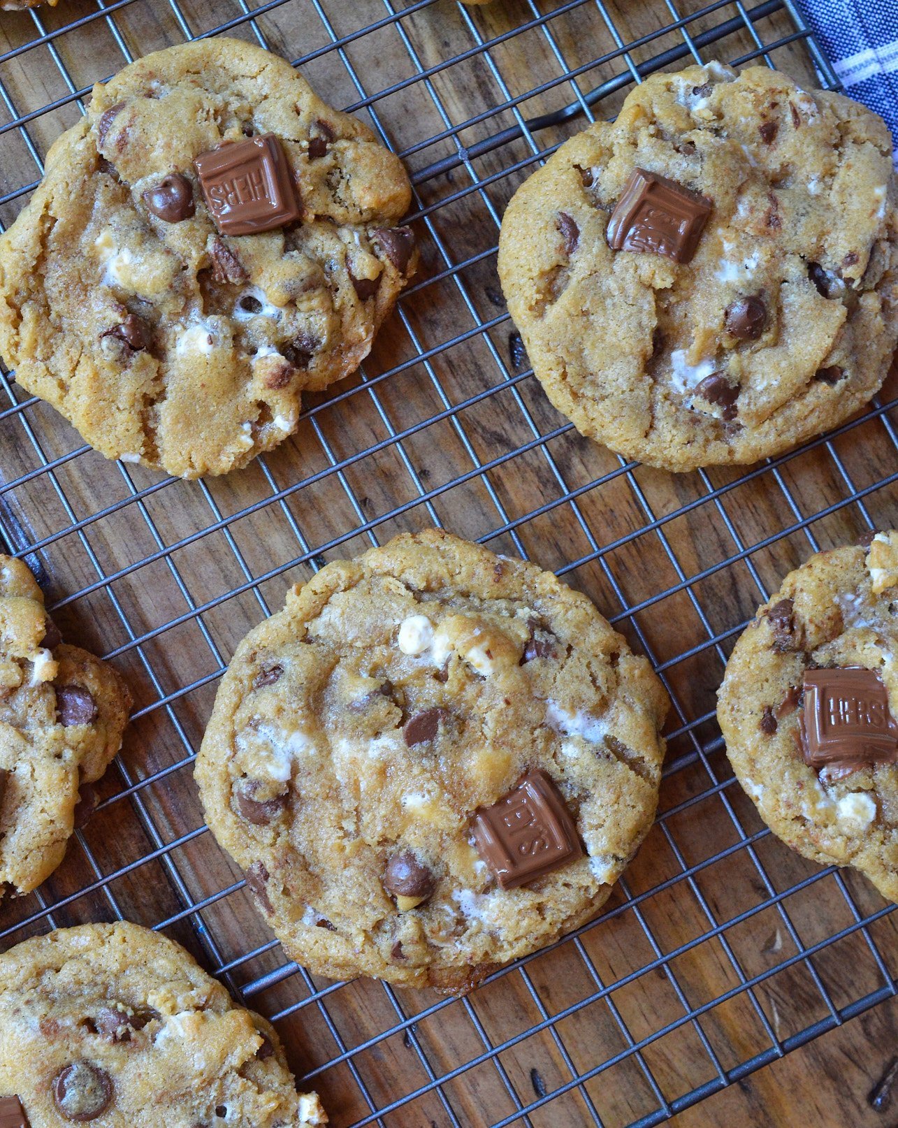 This fun twist on your favorite cookie is filled with S'mores goodness.S'mores Chewy Chocolate Chip Cookies make a great summertime dessert that can be enjoyed inside or outside! Marshmallows, chocolate and graham crackers make this super chewy cookie recipe extra special.
