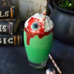 Make this Eye of Toad Halloween Milkshake Recipe for all of your creepy little monsters! This Halloween dessert is made with cookies and cream ice cream, green coloring, whipped cream, red blood gel and topped with a gummy eyeball. This fun recipe is kid approved!