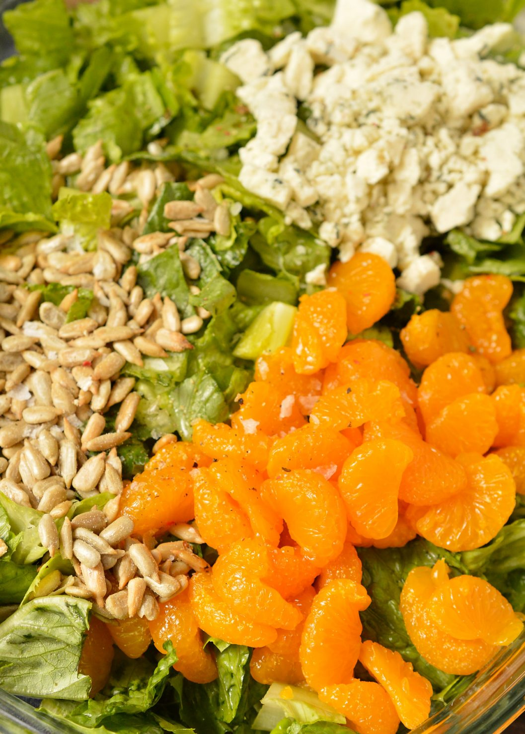 This Balsamic Mandarin Orange Salad may seem like an odd combo, but it works! The creamy balsamic dressing, sunflower seeds, gorgonzola cheese and mandarin oranges are the perfect combo of flavors. This is one of my all-time favorite salads because there is nothing boring about this recipe!