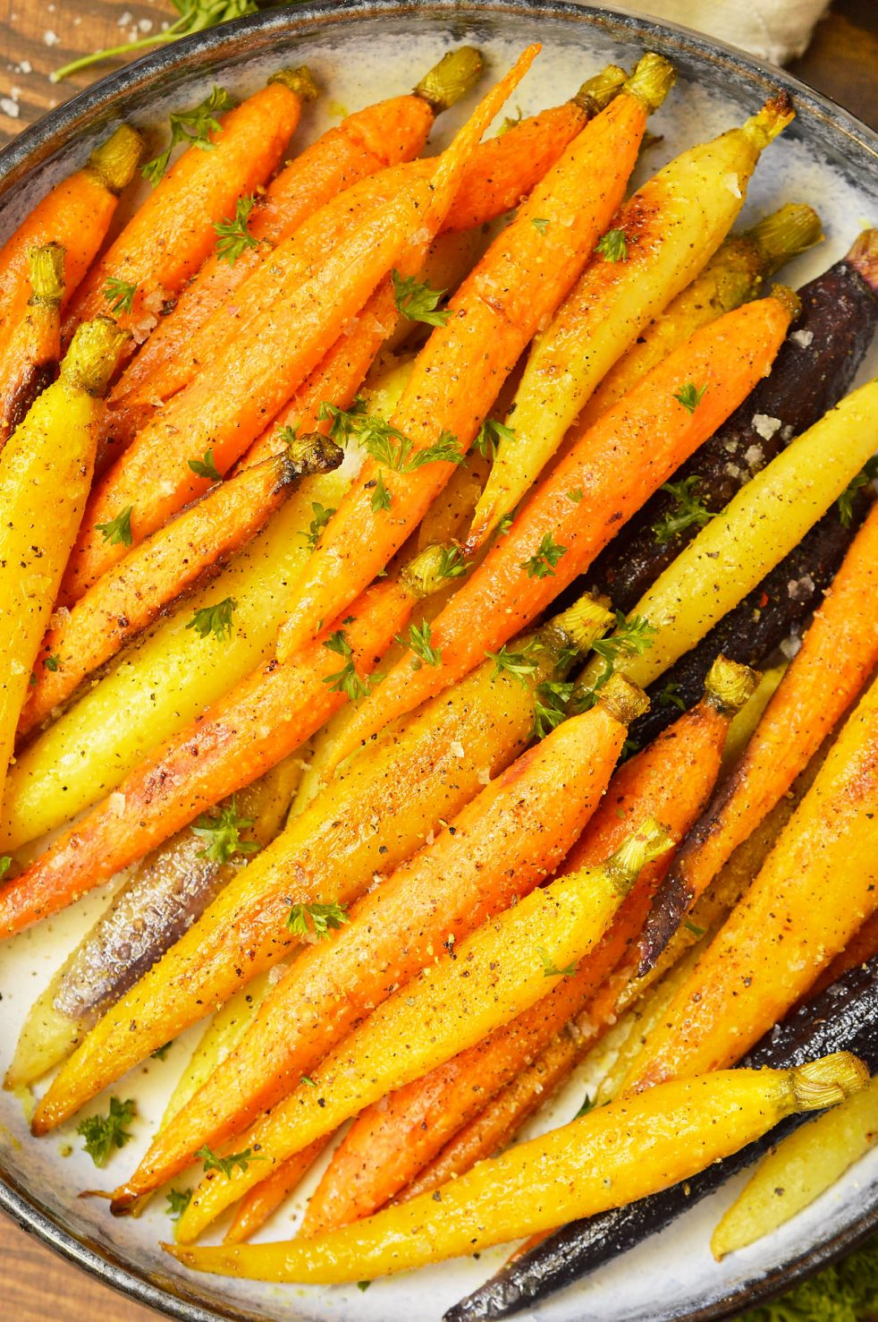 Save some time and make an easy holiday side dish. These Oven Roasted Carrots are a super simple side for your holiday menu or with a weeknight dinner. Rainbow carrots spiced with Adobo seasoning and roasted in the oven. This is a Whole 30 compliant Paleo recipe. #paleorecipe #whole30recipe #roastedcarrots #sidedish #vegan #vegetarian