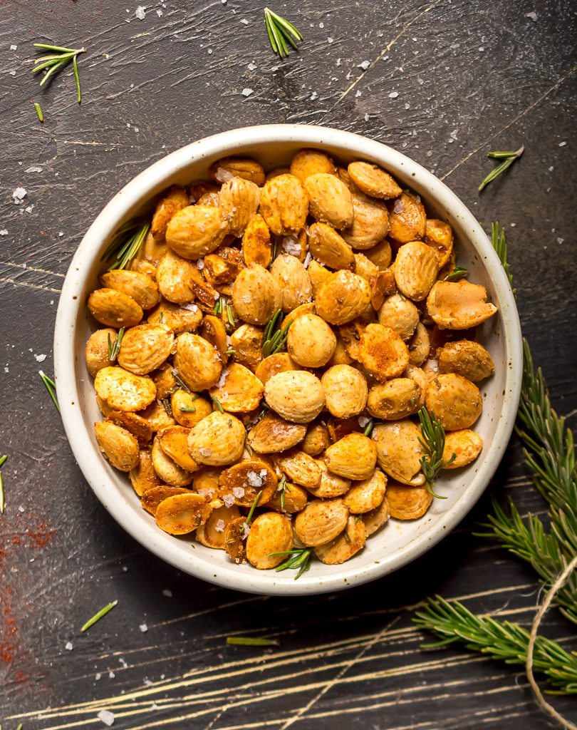 overhead photo of white bowl with golden brown spiced marcona almonds with fresh rosemary in and around the nuts