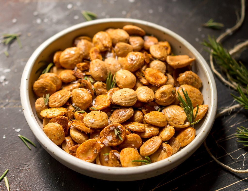 white bowl filled with golden marcona almonds, flaked sea salt and fresh rosemary