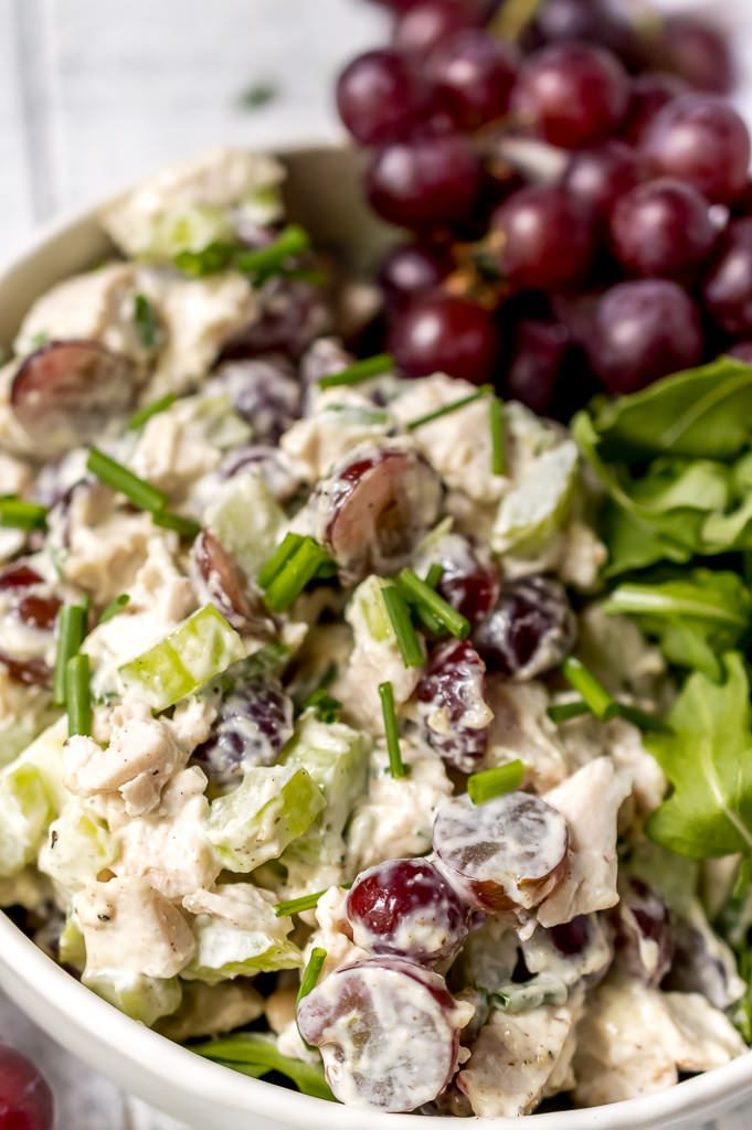extreme close up photo of chicken salad with purple grapes and topped with chopped green chives