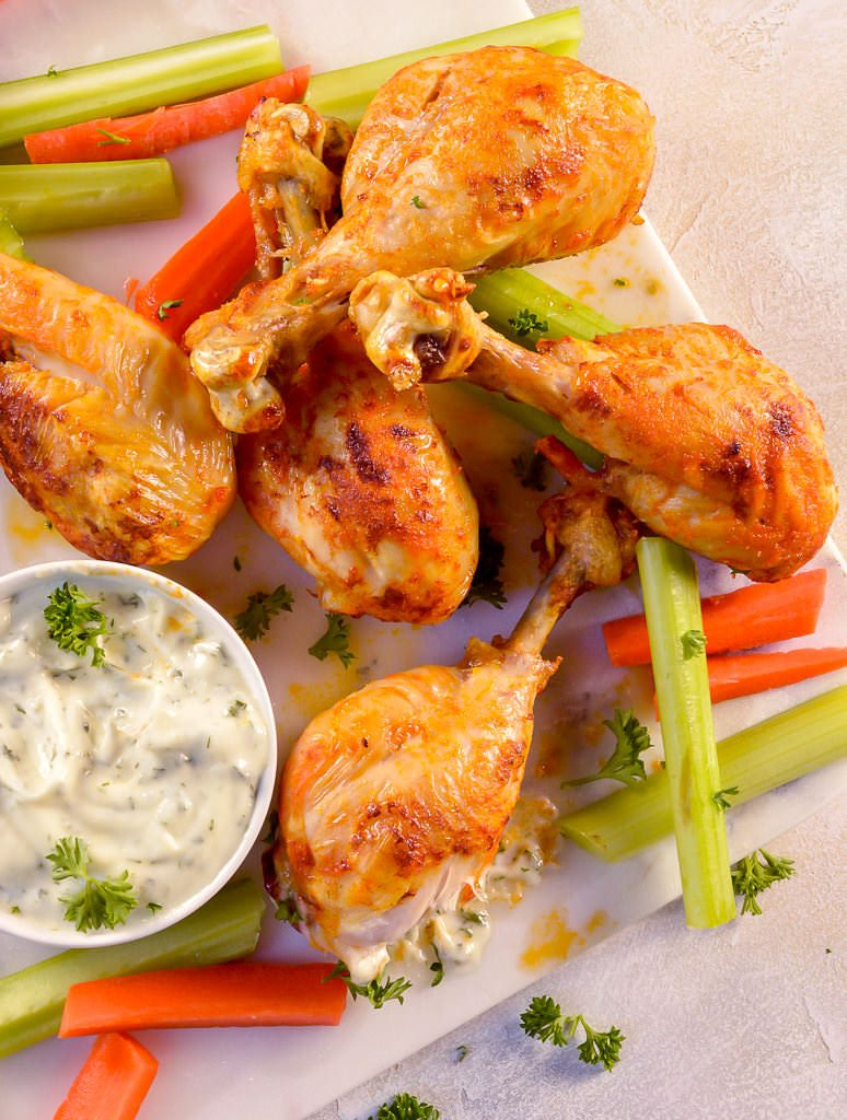 overhead photo of buffalo chicken drumsticks, ranch dip, celery and carrots