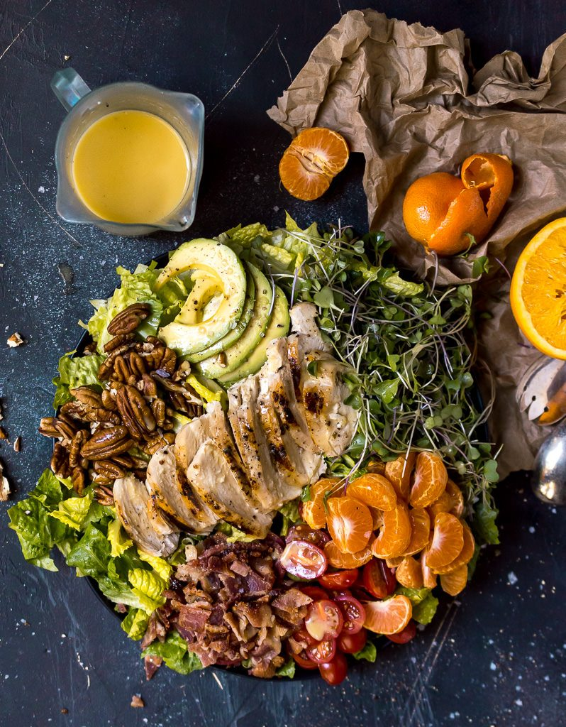 overhead photo of colorful salad and paleo orange maple dressing. mandarin orange half peeled on the side