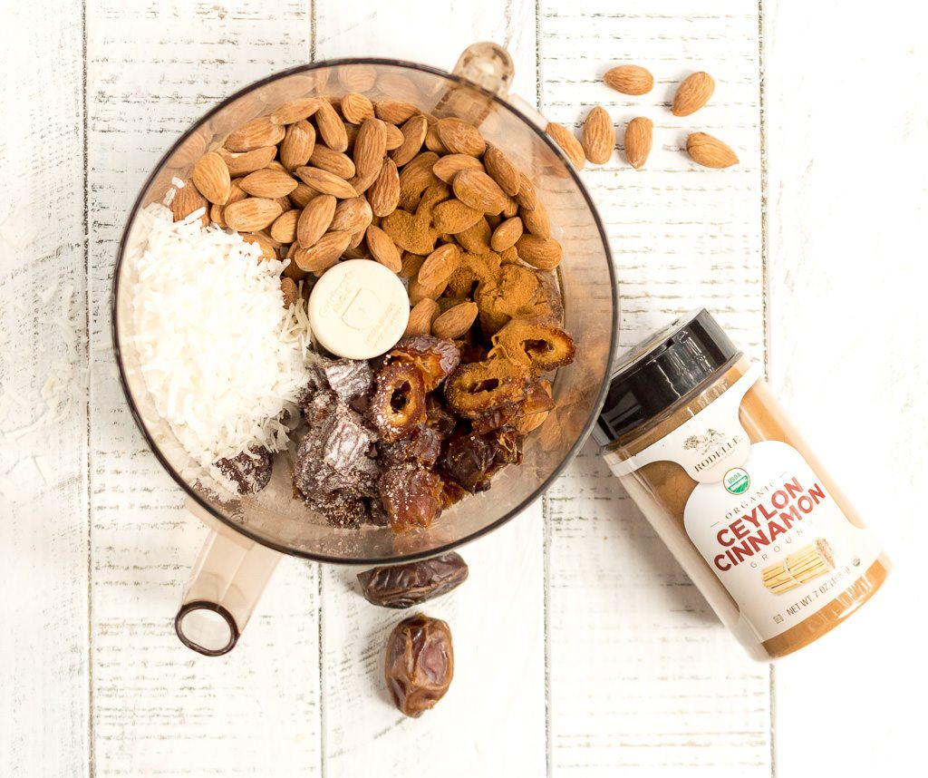overhead photo of food processor containing almonds, dates, coconut with a jar of cinnamon on the side