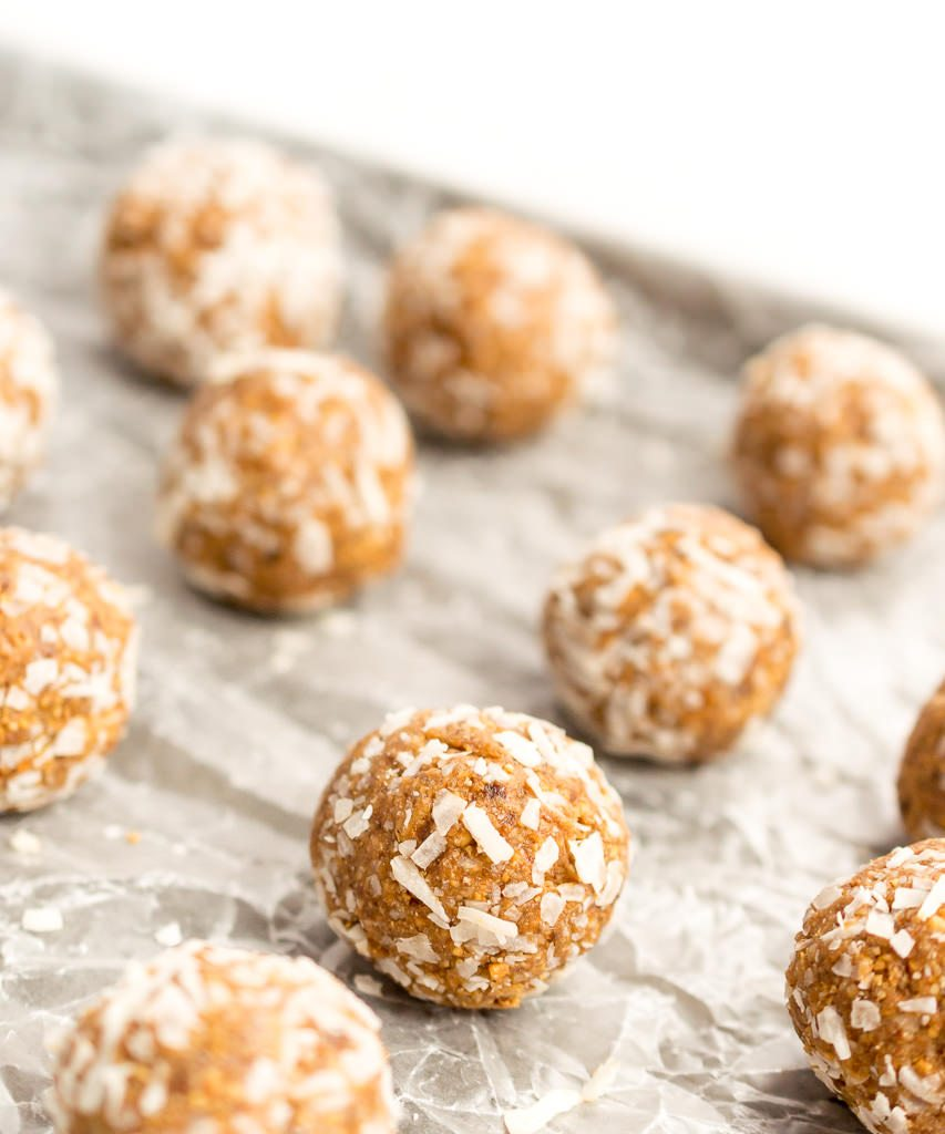 energy balls rolled in coconut on wax lined baking sheet