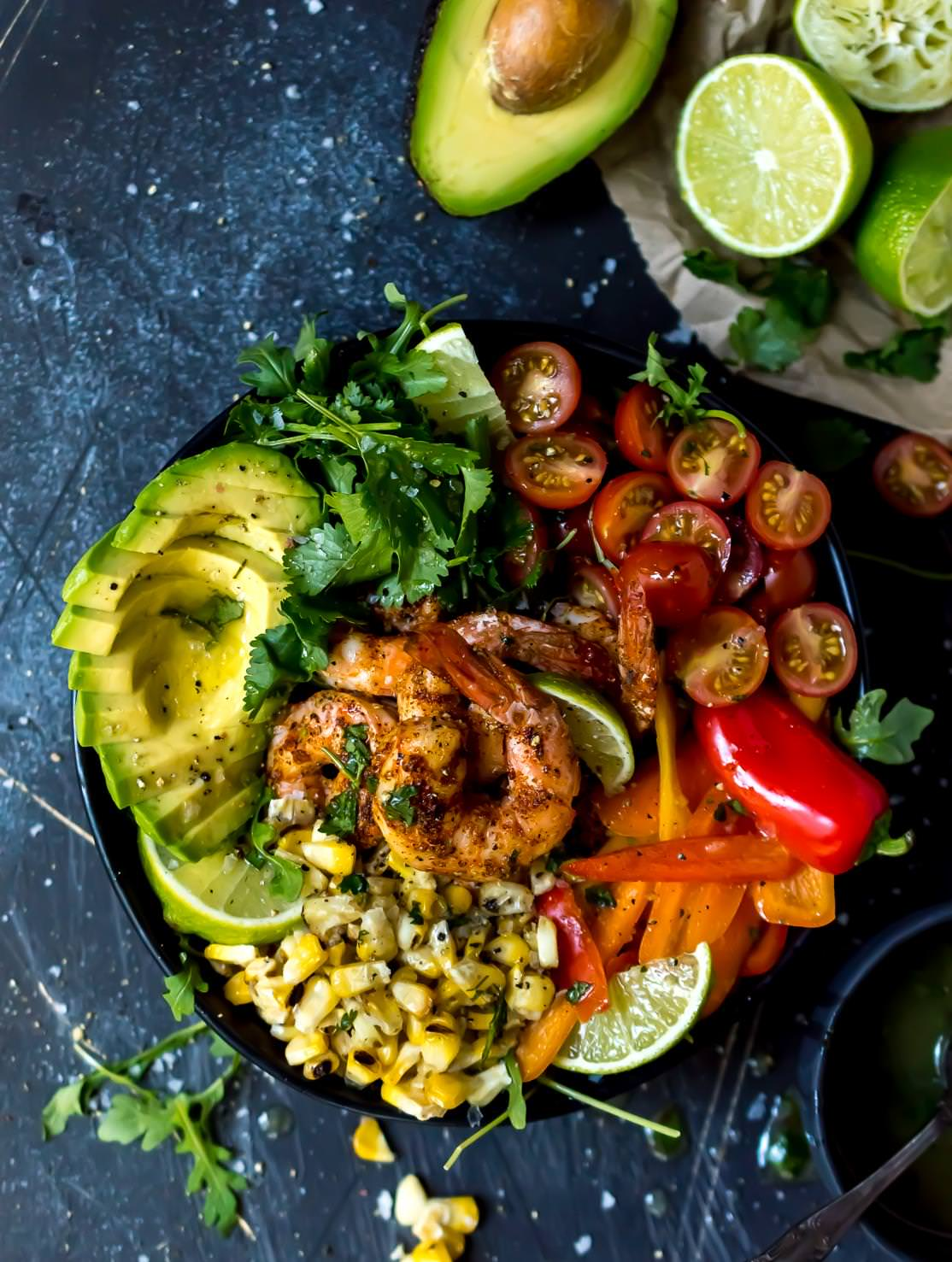 overhead shot of spicy shrimp bowl filled with fresh colorful ingredients, bluish-black background with avocados and limes on the side