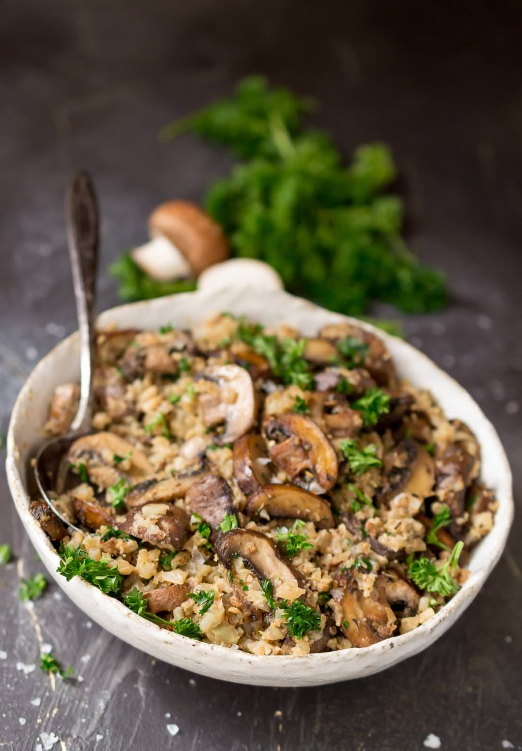 close up photo of cauliflower mushroom rice in white bowl with silver serving spoon. mushroom and parsley in the background