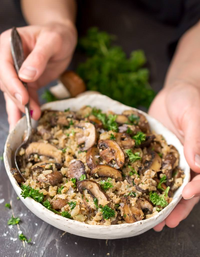 cauliflower mushroom rice in white bowl held by two hands