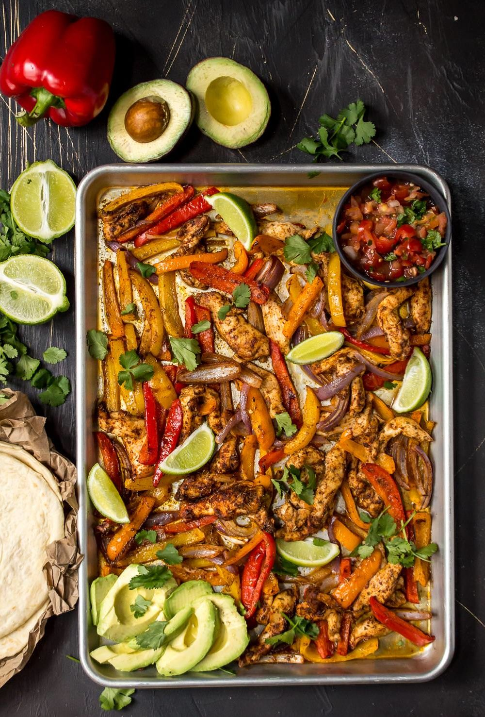 overhead photo of chicken, bell peppers and limes in sheet pan. Tortillas, limes and avocados on the side for chicken fajitas