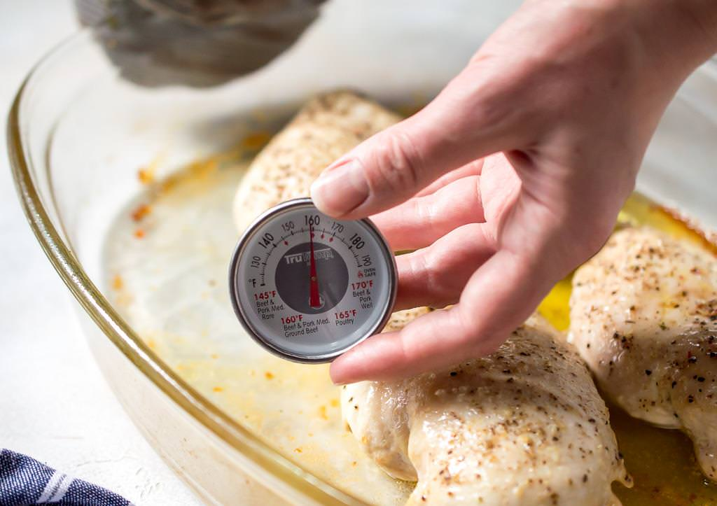 image of checking the temperature of baked chicken breast with a meat thermometer