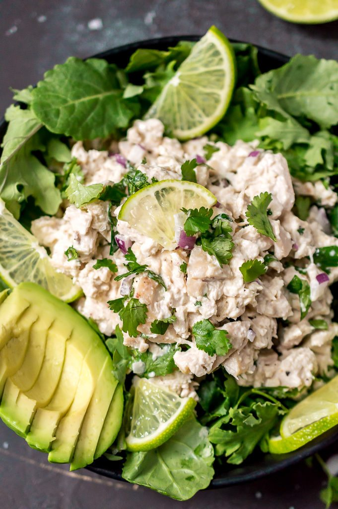 close up photo of cilantro lime chicken salad topped with fresh cilantro, lime wedges and a sliced avocado