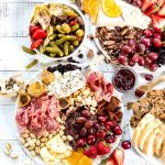 over head photo of cheese board spread on white background. cheese, salami, fresh fruit, dried fruit, nuts, olives, honey and more