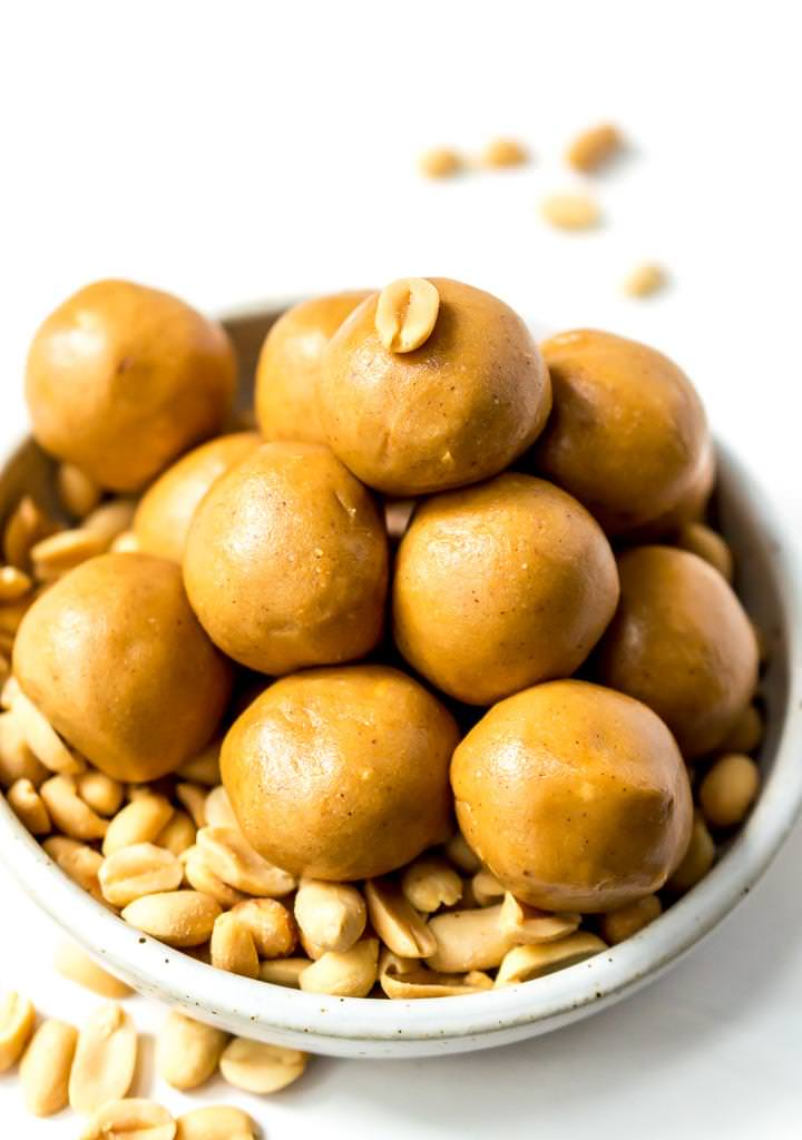 close up photo of peanut butter protein balls in white bowl filled with shelled peanuts