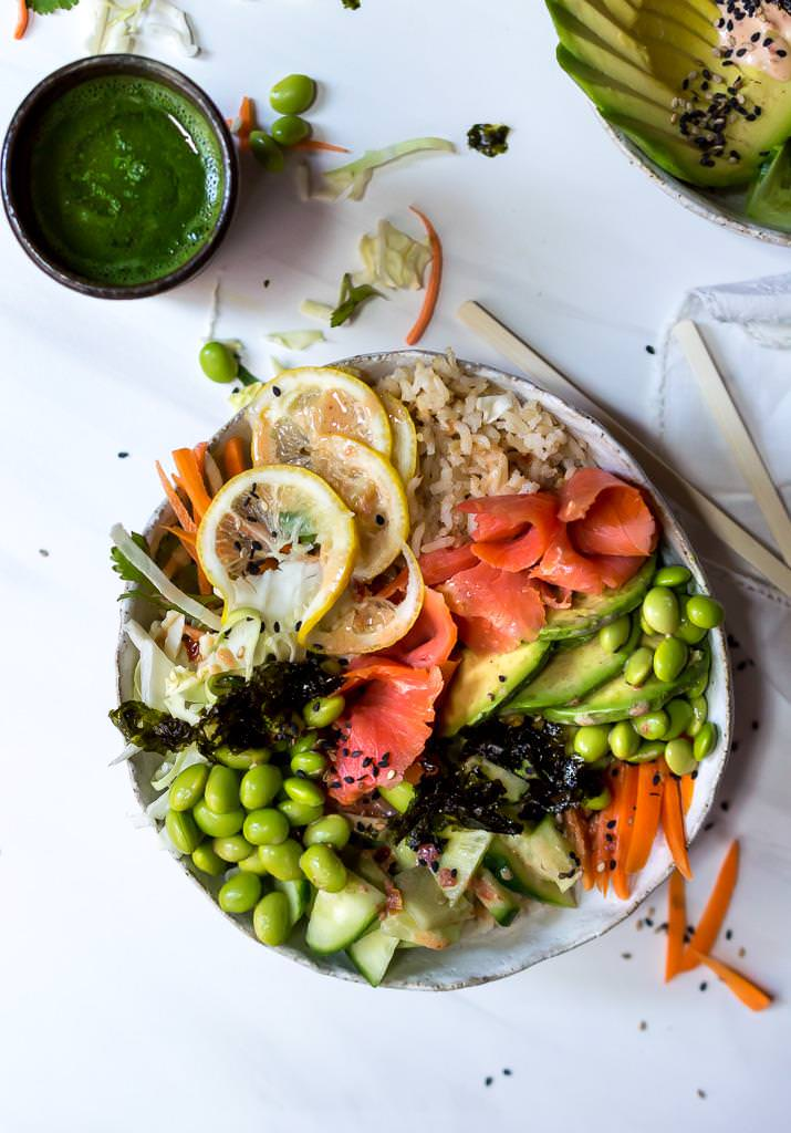 over head photo of salmon sushi roll bowl with mocha green tea and chopsticks on the side