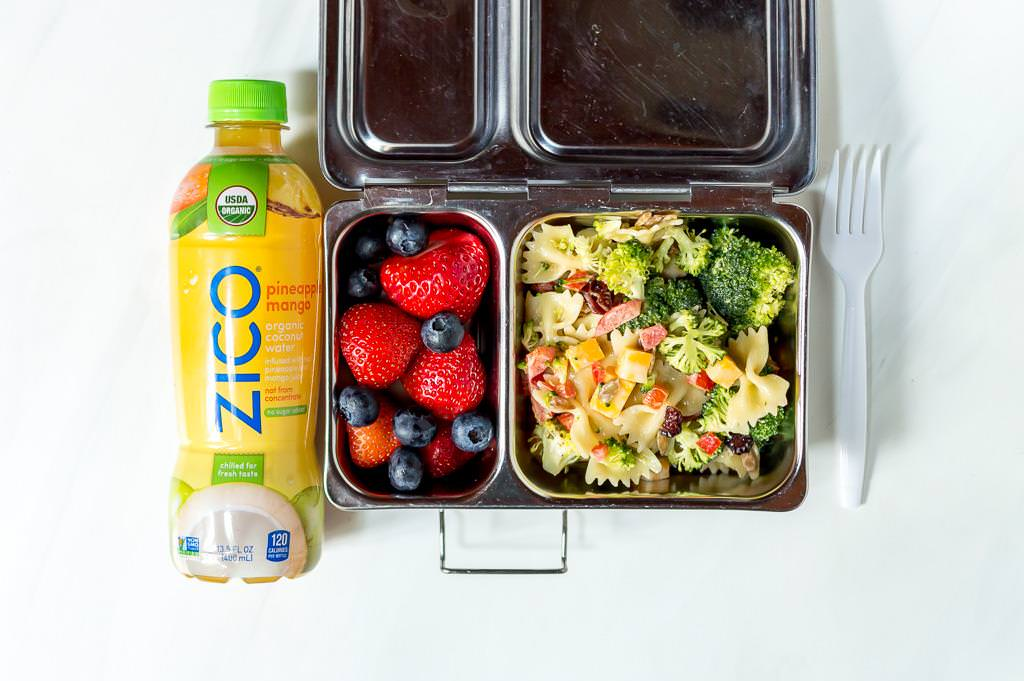 metal lunchbox with broccoli salad recipe and fresh strawberries inside