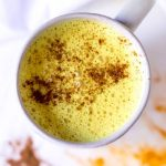 over head photo of golden milk topped with cinnamon in a white mug