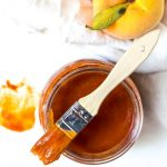 over head photo of peach barbecue sauce recipe in glass jar with bbq brush on top