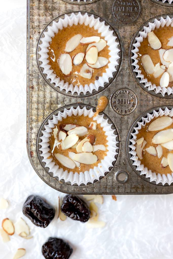 over head photo of almond butter cups in muffin tin with prunes on the side