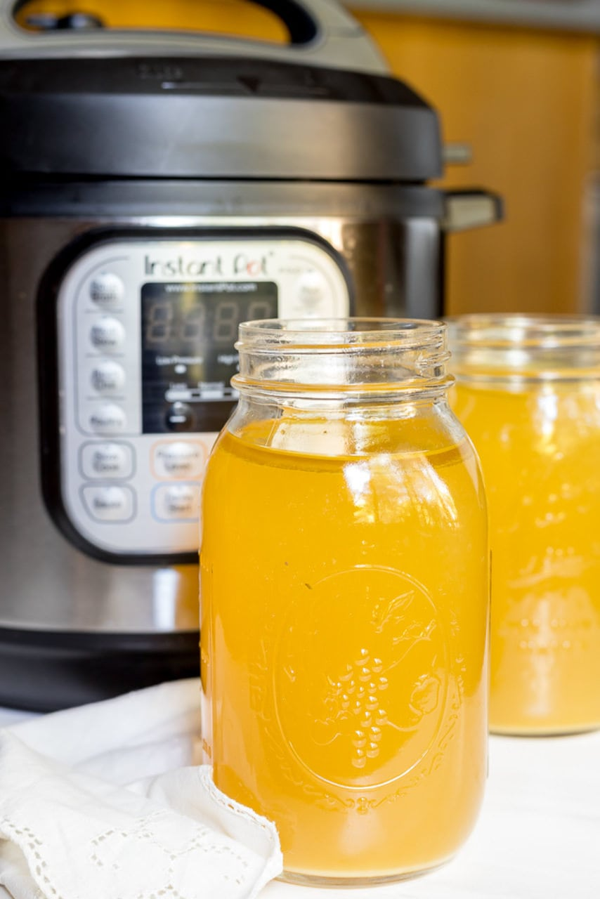 two jars filled with chicken bone broth in front of an Instant Pot pressure cooker