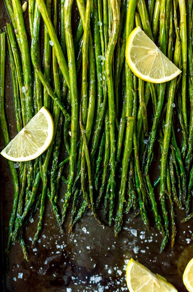 final photo of oven roasted asparagus recipe, close up with lemon wedges on asparagus
