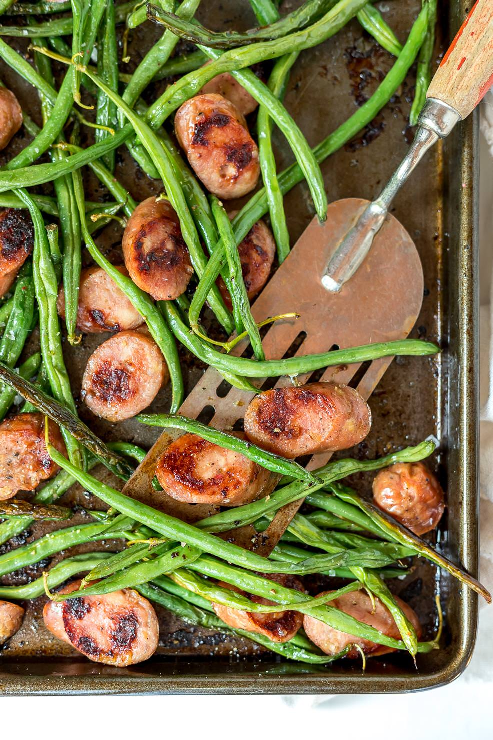 close up of spatula scooping green beans and sausage dinner