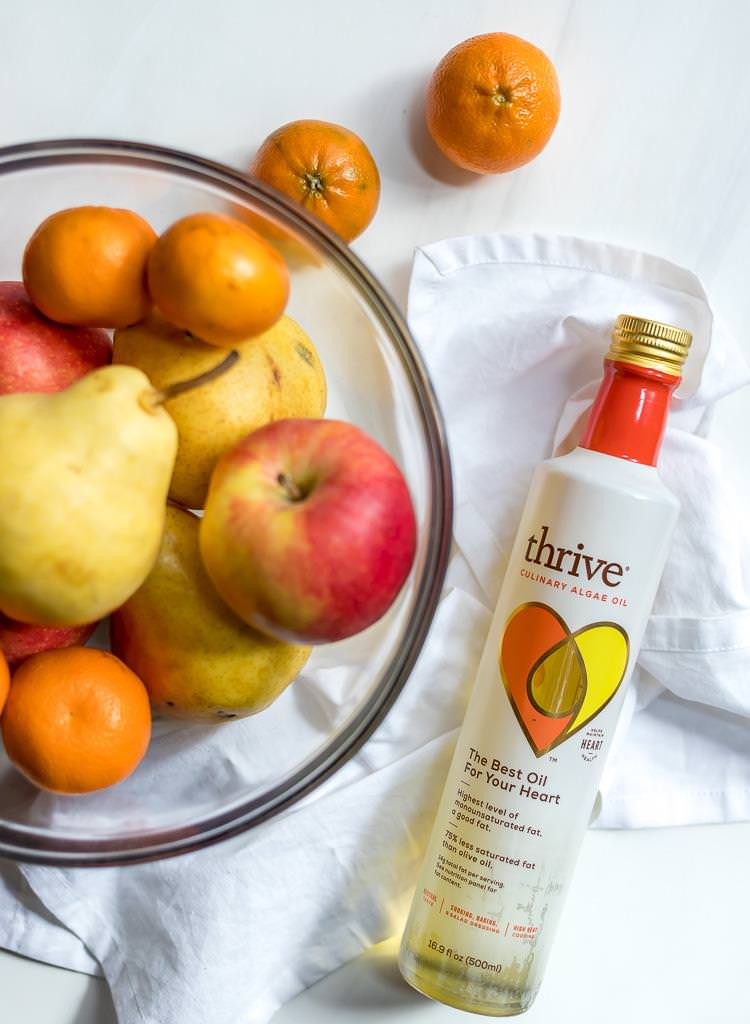 thrive oil next to a glass bowl filled with apples, pears and mandarins