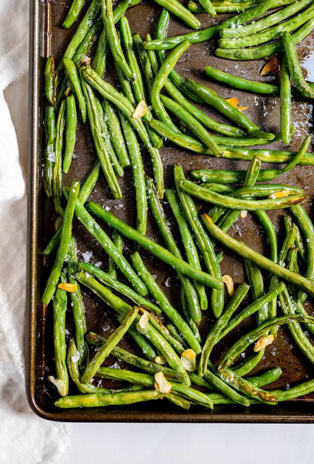 roasted fresh green beans with slices of golden garlic in a dark metal baking sheet