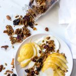 sliced pears and yogurt topped with paleo granola and a jar of granola on the side