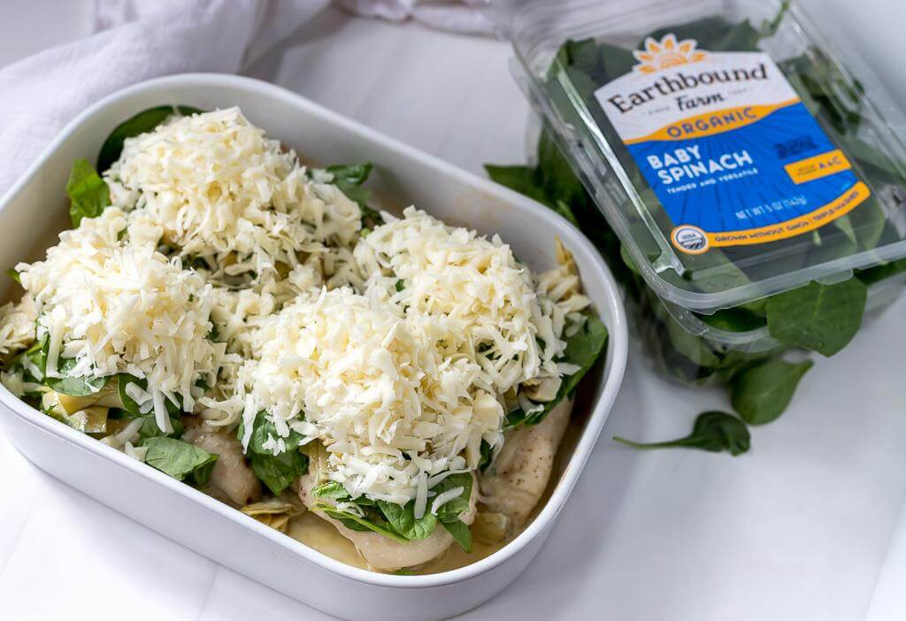 partially baked chicken breast topped with spinach, artichokes and shredded mozzarella cheese