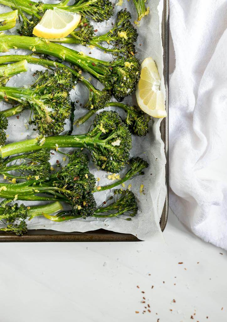 roasted broccolini with lemon wedge on parchment lined pan