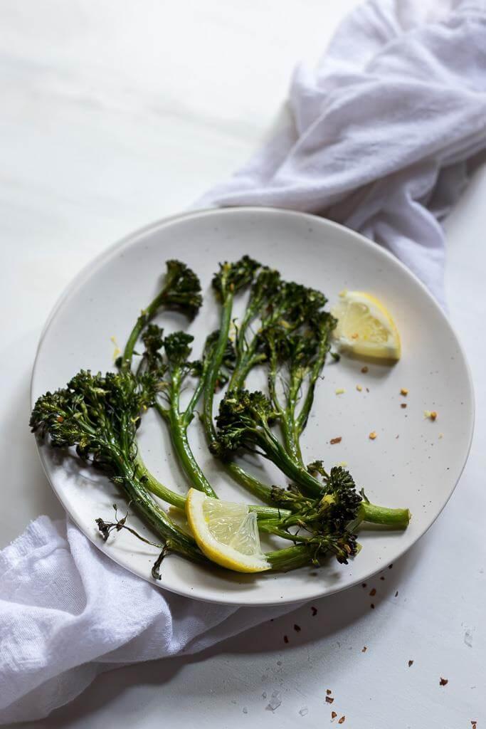 finished roasted broccolini recipe on white plate with lemon wedges