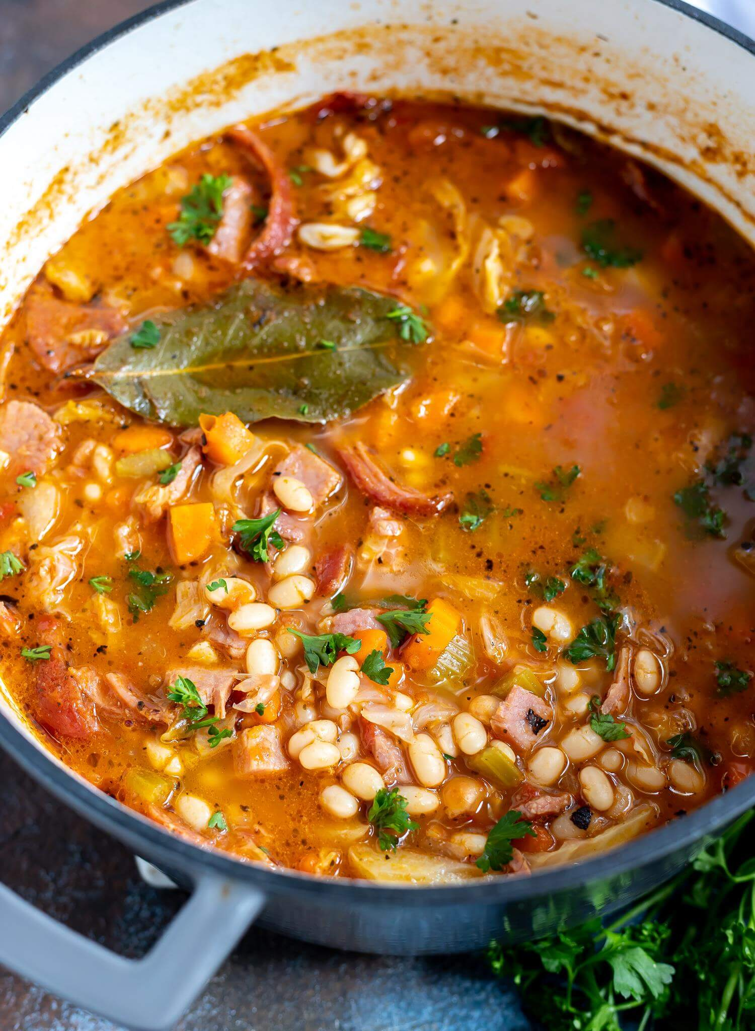 ham and bean soup in pot with bay leaf on top