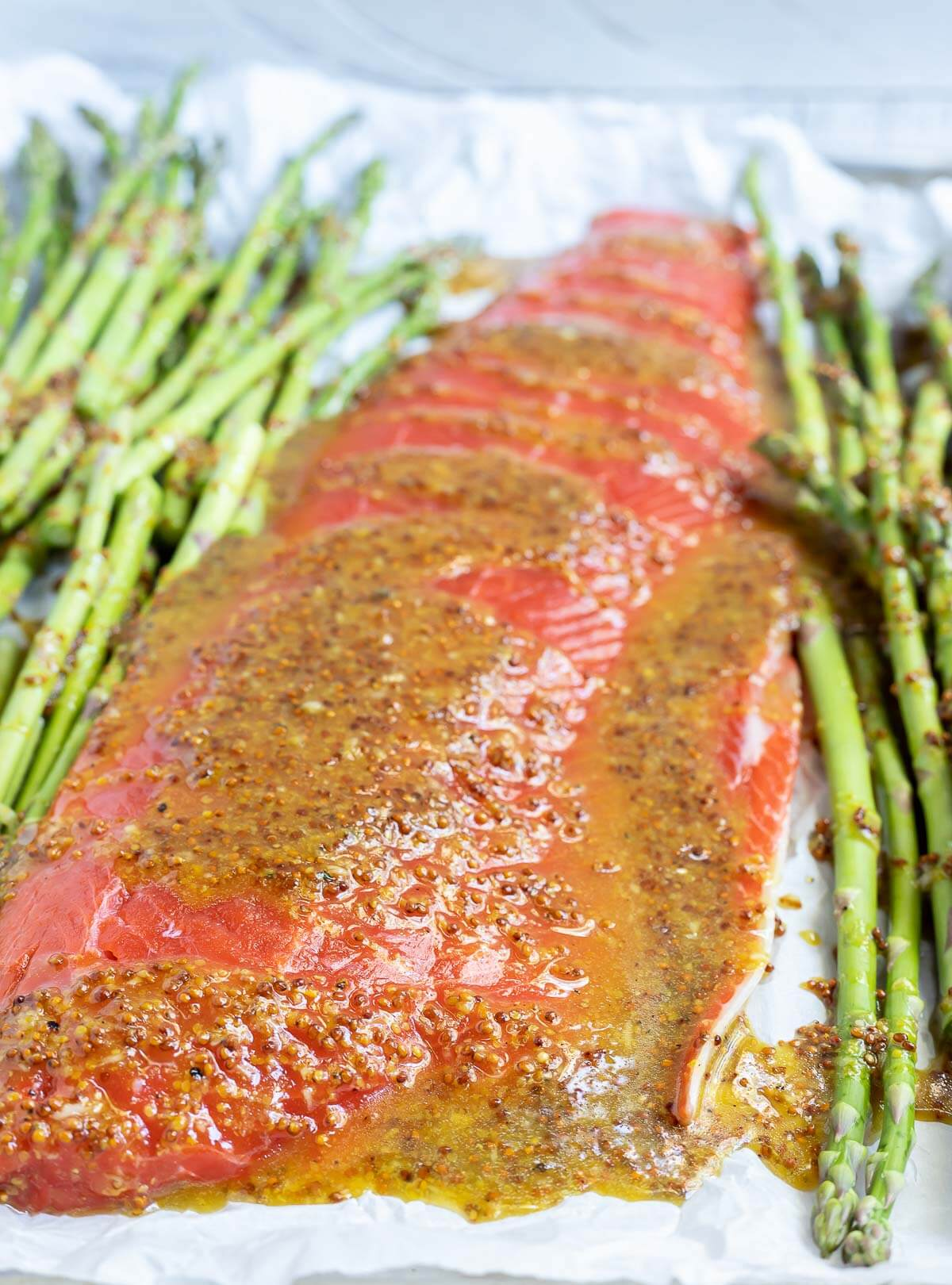 salmon asparagus and sauce on parchment lined sheet pan ready to bake