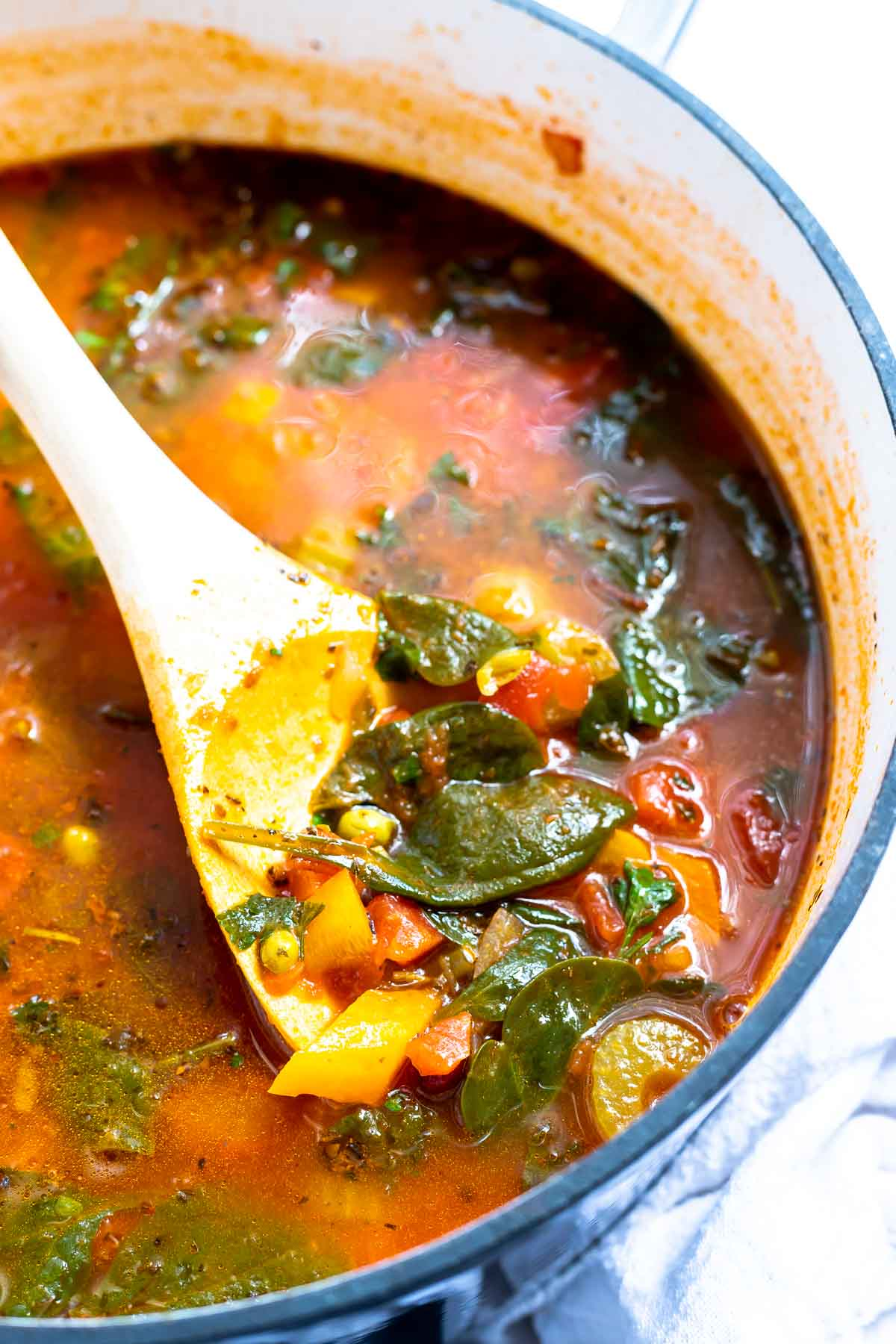 vegetable soup in pot with large wooden spoon