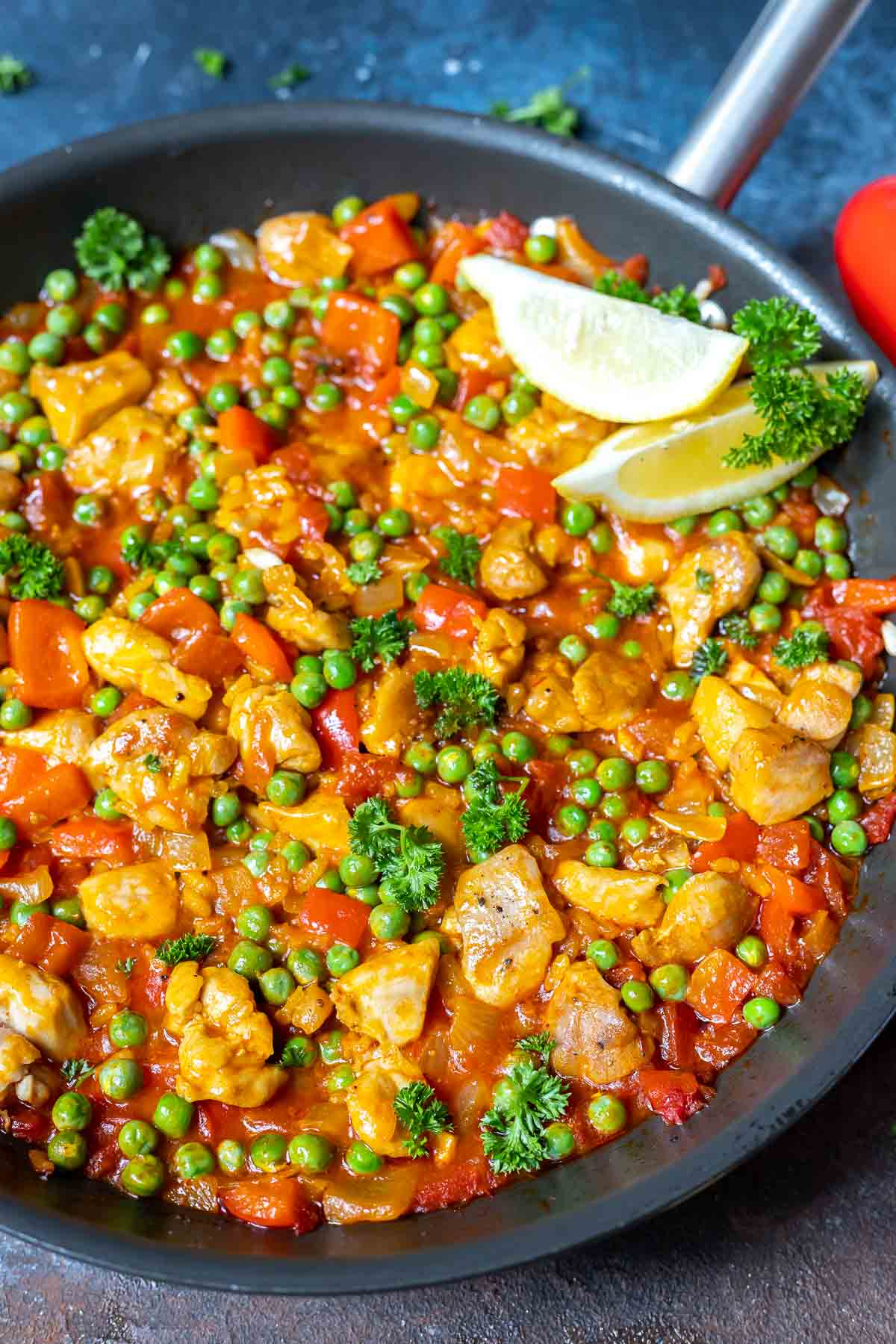 chicken paella in large pan topped with lemons and parsley
