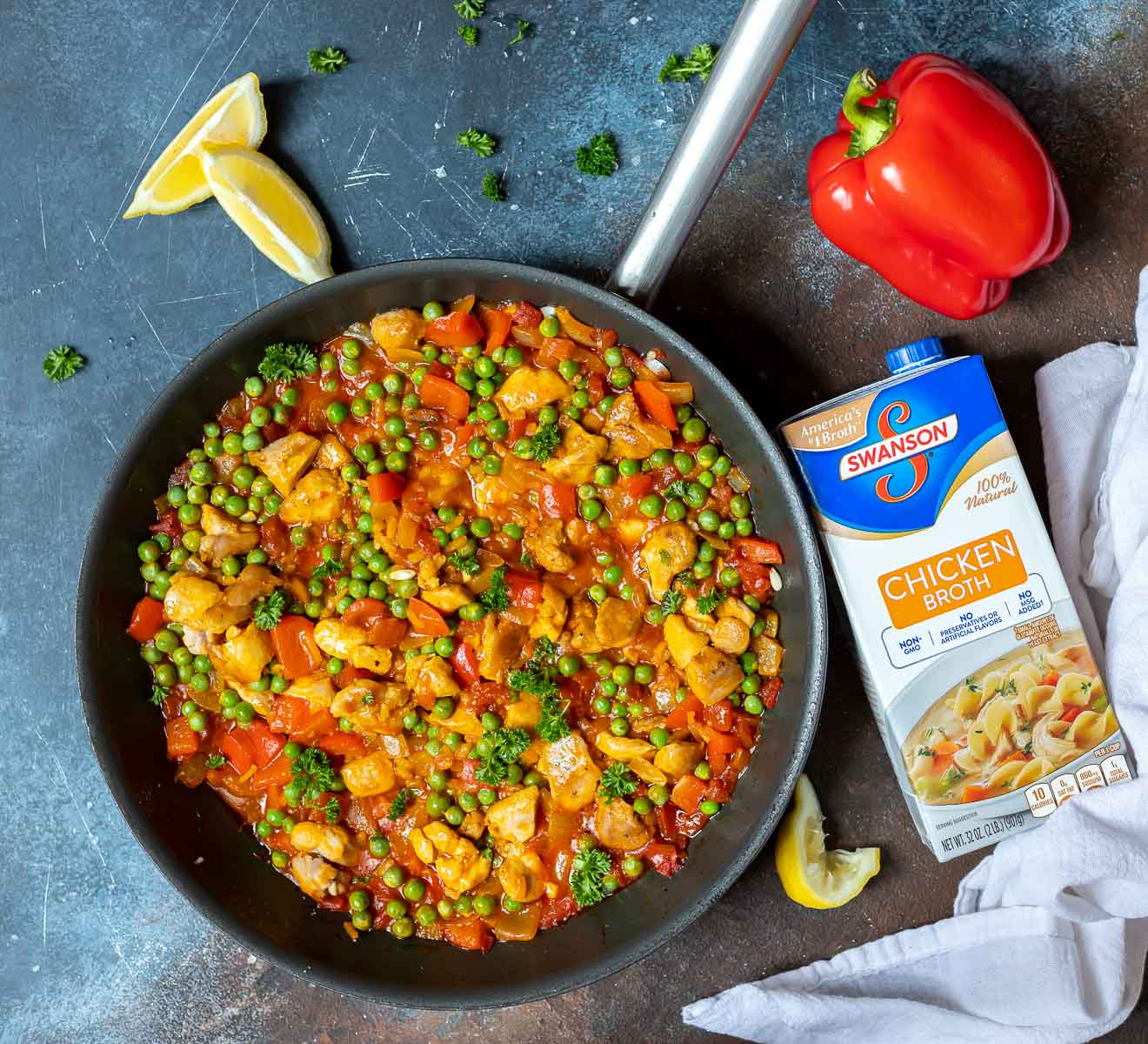 chicken paella in pan with chicken broth container on the side