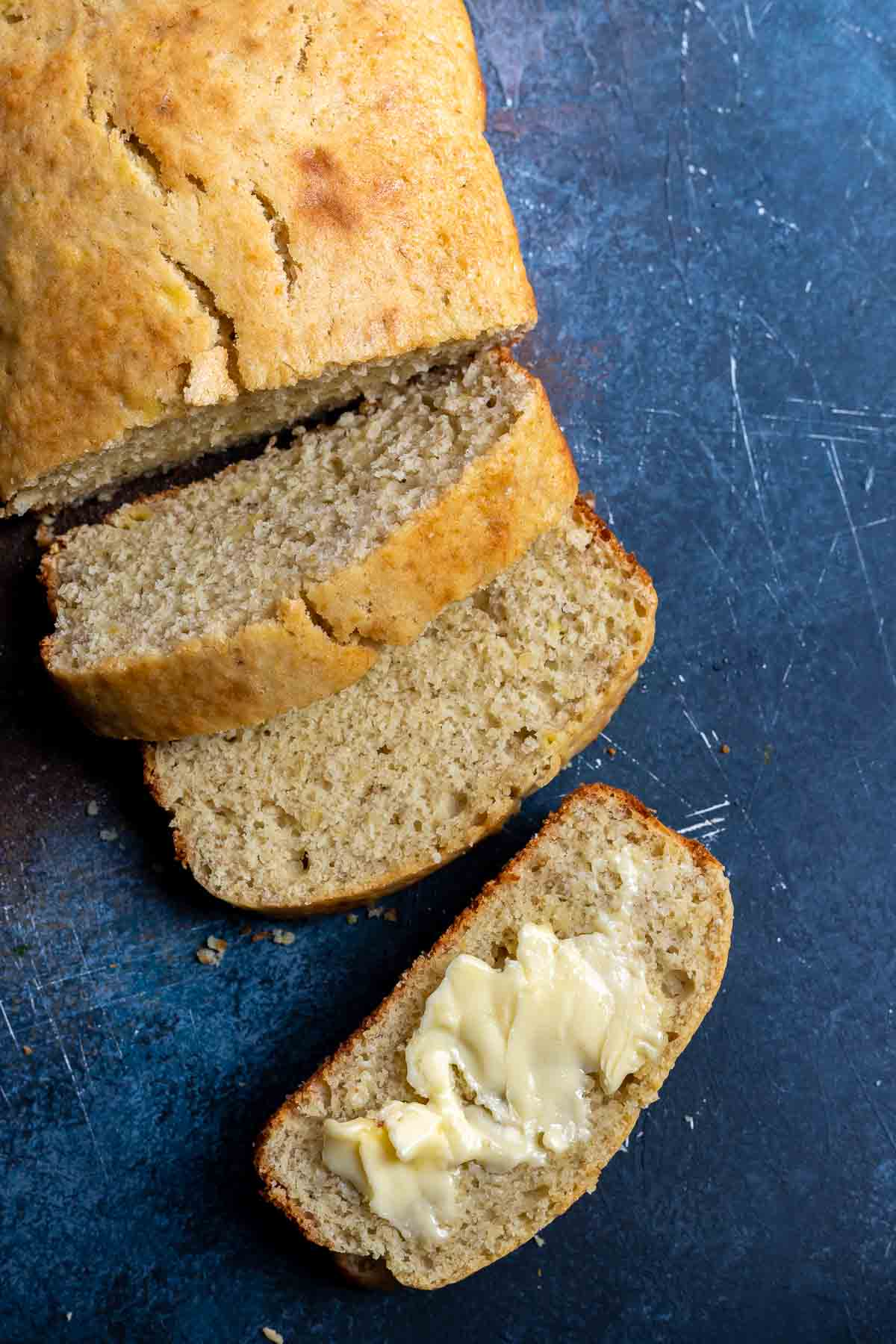 simple banana bread loaf sliced, one slice with butter on top