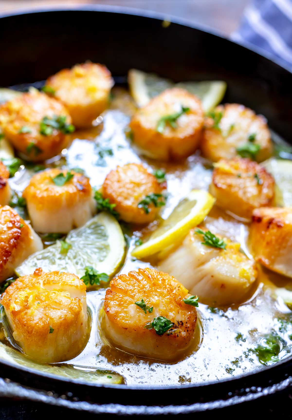 pan seared scallops in buttery sauce with lemon slices and parsley